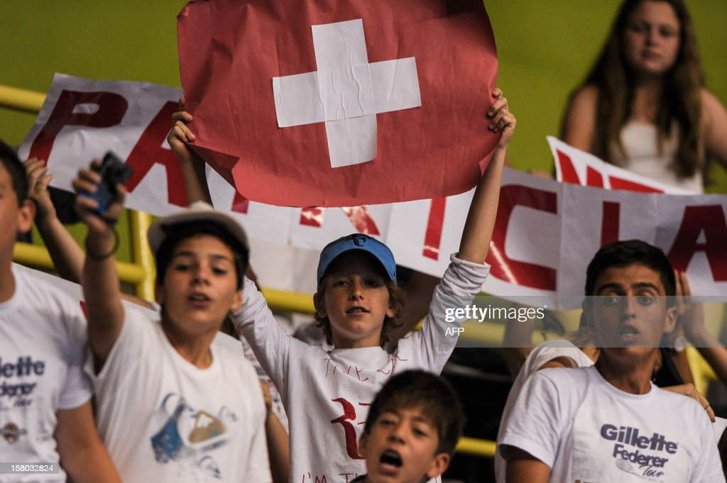 Fans of Swiss tennis player Roger Federer cheer during an exhibition match against German Tommy Haas, at the Ibirapuera Gymnasium in Sao Paulo, Brazil, on December 9, 2012. AFP PHOTO/Yasuyoshi CHIBA