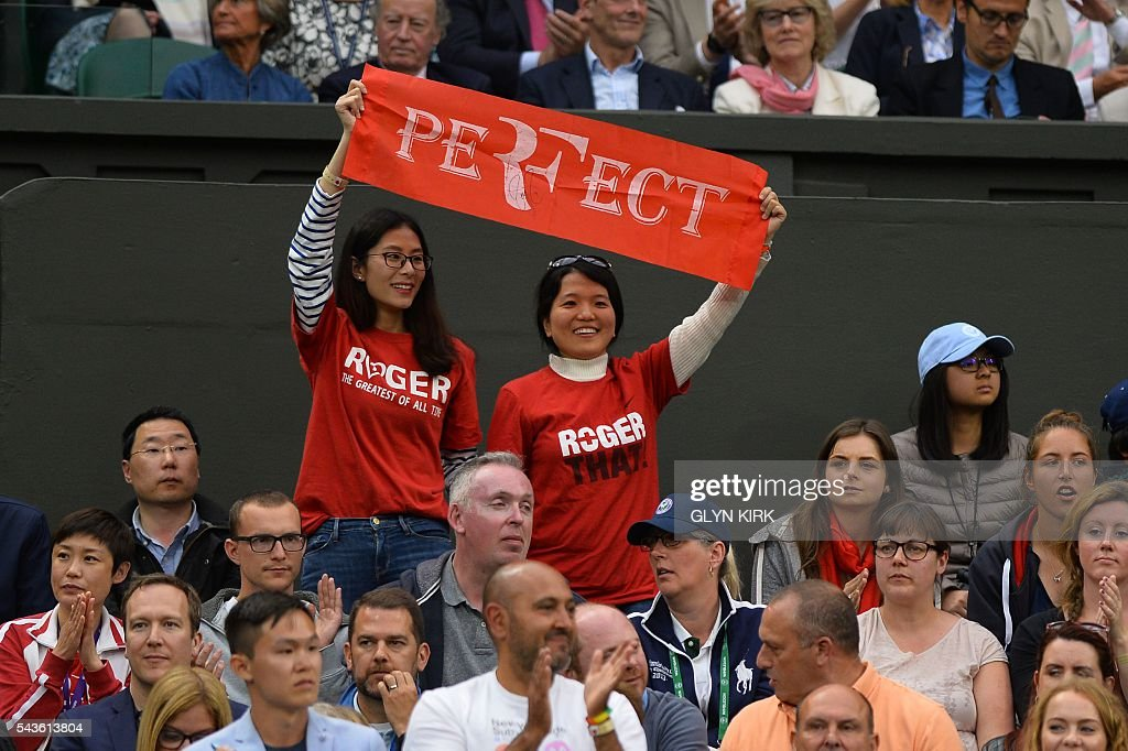 Fans of Switzerland's Roger Federer hold up a sign as Federer plays against Britain's Marcus Willis in their men's singles second round match on the third day of the 2016 Wimbledon Championships at The All England Lawn Tennis Club in Wimbledon, southwest London, on June 29, 2016. / AFP / GLYN