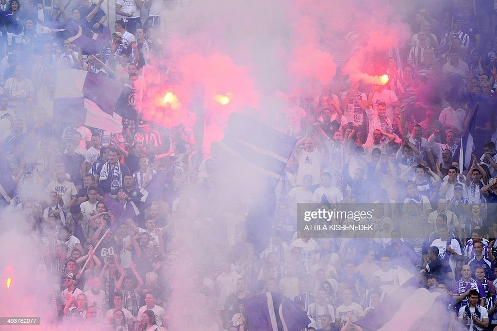 Fans of TE Ujpest celebrates scoring during the Hungarian Cup final football match VTK Disosgyor vs TE Ujpest on May 25, 2014 at the Puskas stadium in Budapest.