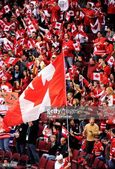 Fans of team Canada hold up flags and signs in the stands during the ice hockey men's preliminary game between Canada and Norway on day 5 of the...