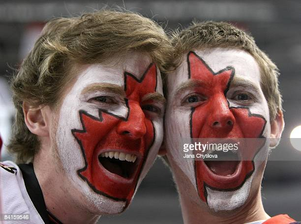 Fans of Team Canada with a Canadian flag painted on their faces yell during the Team Canada game against Team USA during the 2009 IIHF World Junior...