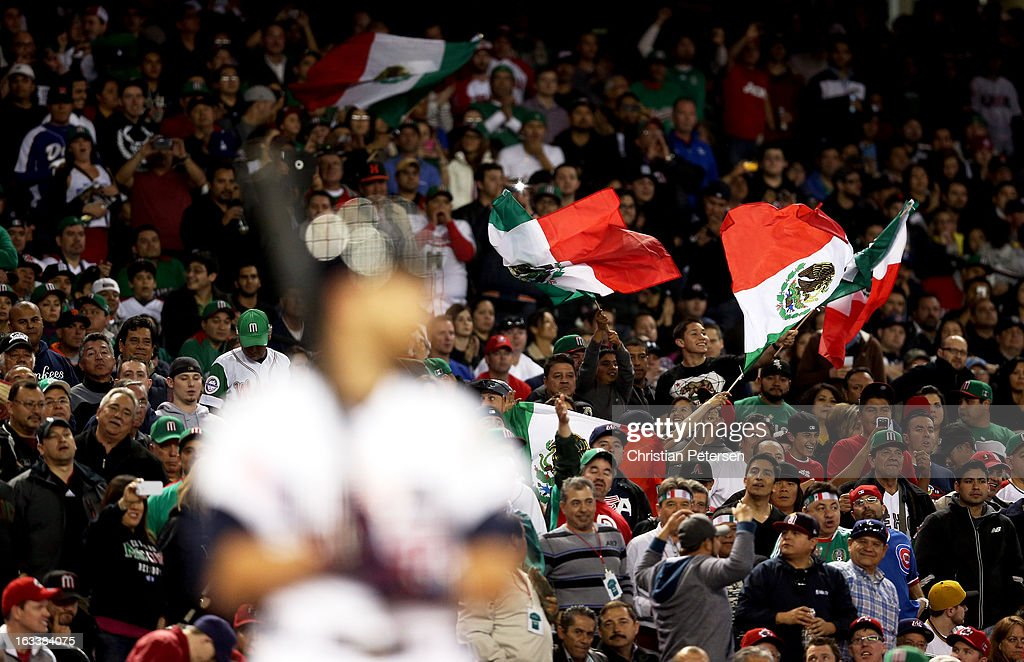 Fans of team Mexico waves flags in support of Mexico as <a gi-track='captionPersonalityLinkClicked' href=/galleries/search?phrase=Jonathan+Lucroy&family=editorial&specificpeople=5732413 ng-click='$event.stopPropagation()'>Jonathan Lucroy</a> #22 of the United States bats in the ninth inning during the World Baseball Classic First Round Group D game at Chase Field on March 8, 2013 in Phoenix, Arizona.