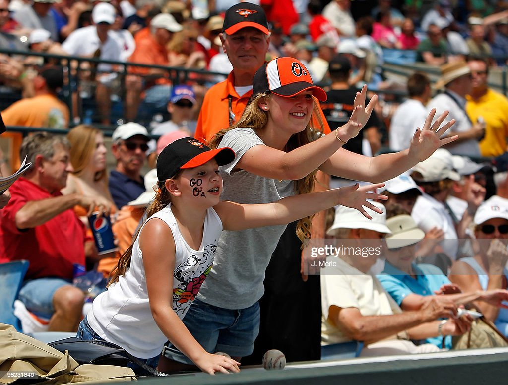 Fans of the Baltimore Orioles call for a ball just before the start of the Grapefruit League Spring Training Game against the New York Mets at Ed...