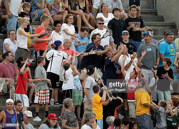 Fans of the Boston Cannons reach for free gifts during a game with the Hamilton Nationals at Harvard Stadium on July 23 2011 in Boston Massachusetts