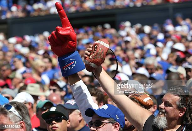 Fans of the Buffalo Bills hold up a deflated football during NFL game action against the New England Patriots at Ralph Wilson Stadium on September 20...