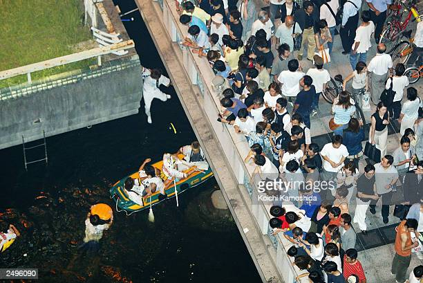 Fans of the Central League baseball club team Hanshin Tigers gather to watch as fans jump into the Dotombori River on Sept 15 2003 in central Osaka...