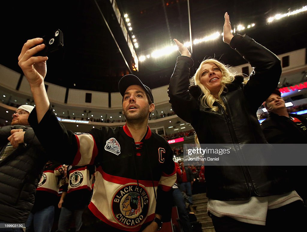 Fans of the Chicago Blackhawks cheer and take pictures after a win over the St. Louis Blues at the United Center on January 22, 2013 in Chicago, Illinois. The Blackhawks defeated the Blues 3-2.