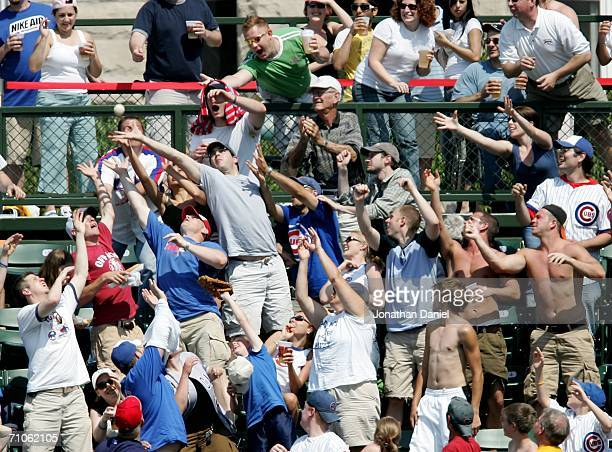 Fans of the Chicago Cubs scramble to catch a home run ball in the right field bleachers hit by Freddie Bynum of the Cubs against the Atlanta Braves...