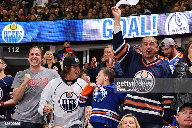 Fans of the Edmonton Oilers celebrate the Oilers' fourth goal against the New Jersey Devils during an NHL game at Rexall Place on October 7 2013 in...