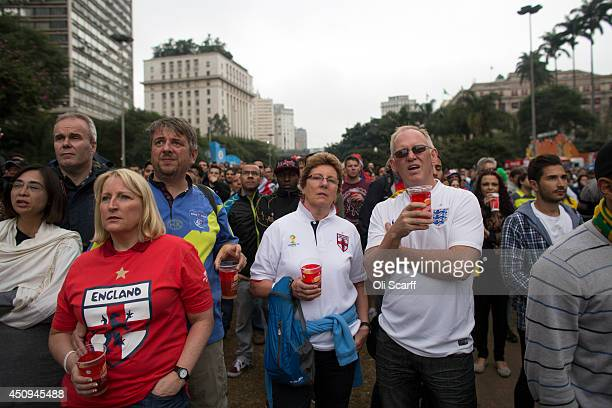Fans of the England football team watch a match on a giant screen in the Fan Fest area in central Sao Paulo between Costa Rica and Italy on June 20...