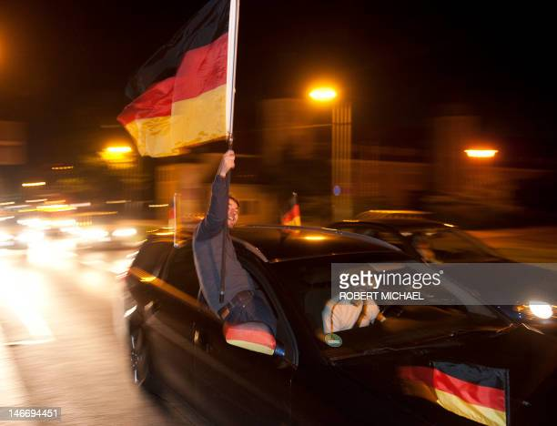 Fans of the German national football team celebrate with national flag in a car in Dresden eastern Germany after their team won their EURO 2012...