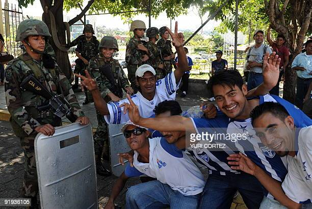 Fans of the Honduran national football team pose for a picture in front of soldiers standing guard outside the presidential palace in Tegucigalpa on...