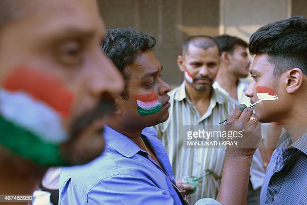 Fans of the Indian cricket team get their faces painted in the colours of the Indian flag as they prepare to cheer their team on the eve of the...