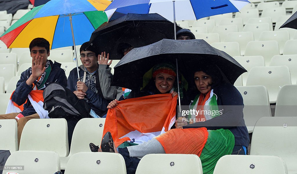 Fans of the Indian cricket team shelter under umbrellas as rain delays the start of play in the 2013 ICC Champions Trophy Final cricket match between England and India at Edgbaston in Birmingham, central England on June 23, 2013. AFP PHOTO/PAUL ELLIS - RESTRICTED TO EDITORIAL USE -