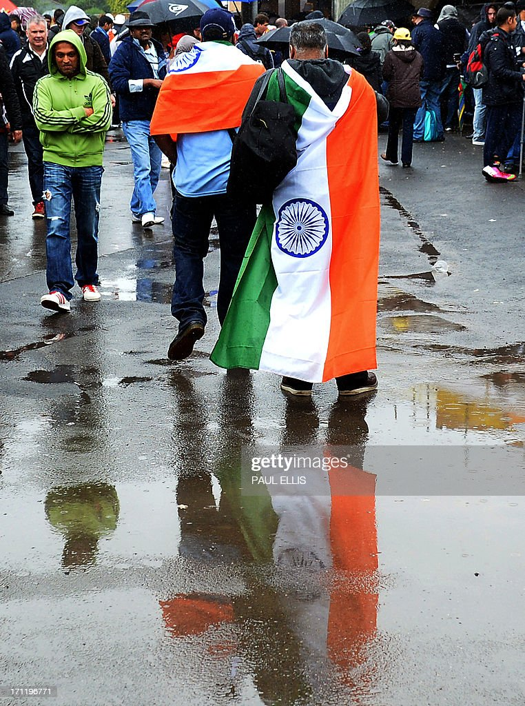 Fans of the Indian cricket team walk through the puddles as rain delays the start of play in the 2013 ICC Champions Trophy Final cricket match between England and India at Edgbaston in Birmingham, central England on June 23, 2013.