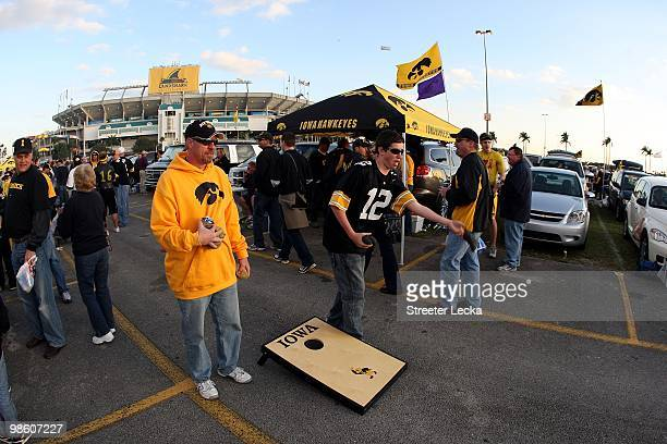 Fans of the Iowa Hawkeyes play a bean bag toss game in the parking lot while tailgating prior to the FedEx Orange Bowl against the Georgia Tech...