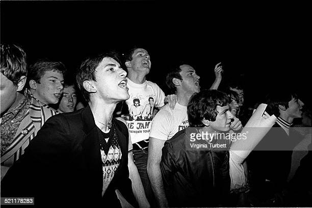 Fans of The Jam cheering at the front of the audience wearing mod clothes and Jam tshirts at Wembley Arena London 5 December 1982