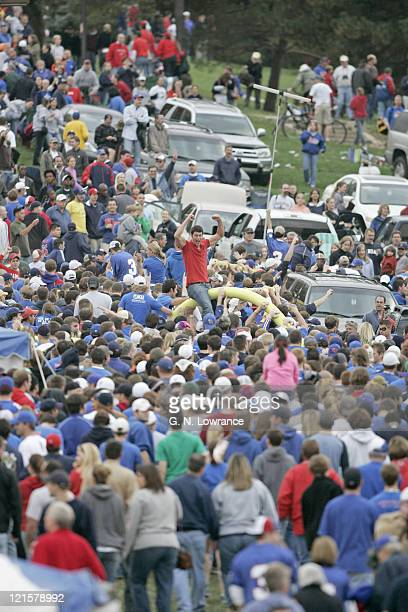 Fans of the Kansas Jayhawks carry a goal post towards campus following a win over the Nebraska Cornhuskers at Memorial Stadium in Lawrence Kansas on...