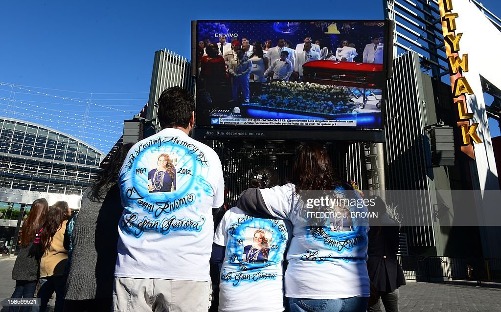 Fans of the late Mexican-American singer Jenni Rivera mourn her death while watching a live viewing of the memorial service at the Gibson Amphitheater in Universal City, Los Angeles, on December 19, 2012 in California, attended by those with tickets. The service, billed by the Rivera family as a 'Celestial Graduation,'' was broadcast live and watched by her many fans off a big screen at a Universal CityWalk plaza. AFP PHOTO / Frederic J. BROWN