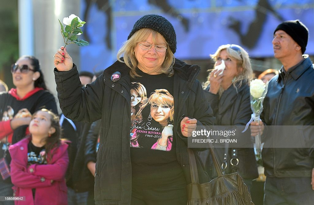 Fans of the late Mexican-American singer Jenni Rivera mourn her death while watching a live viewing of the memorial service at the Gibson Amphitheater in Universal City on December 19, 2012 in California, attended by those with tickets. The service, billed by the Rivera family as a 'Celestial Graduation,'' was broadcast live and watched by her many fans off a big screen at a Universal CityWalk plaza. AFP PHOTO / Frederic J. BROWN