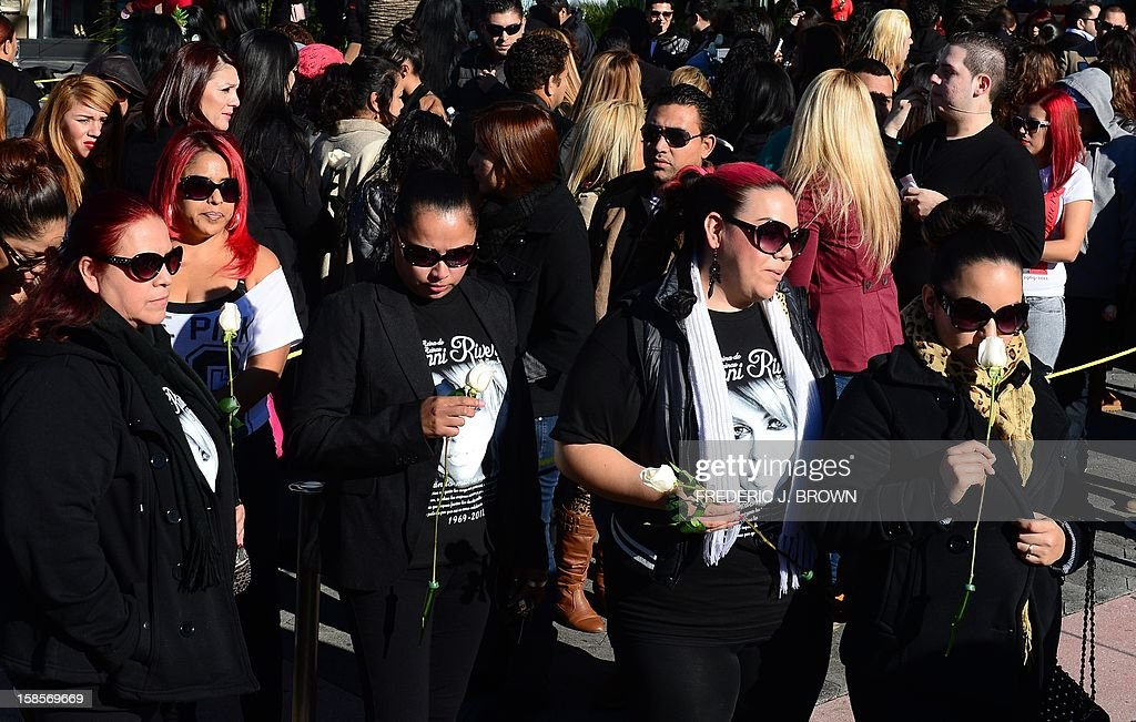 Fans of the late Mexican-American singer Jenni Rivera wait in line with their tickets to attend the memorial service at the Gibson Amphitheater in Universal City on December 19, 2012 in California. The service, billed by the Rivera family as a 'Celestial Graduation,'' was broadcast live and watched by her many fans off a big screen at a Universal CityWalk plaza. AFP PHOTO / Frederic J. BROWN
