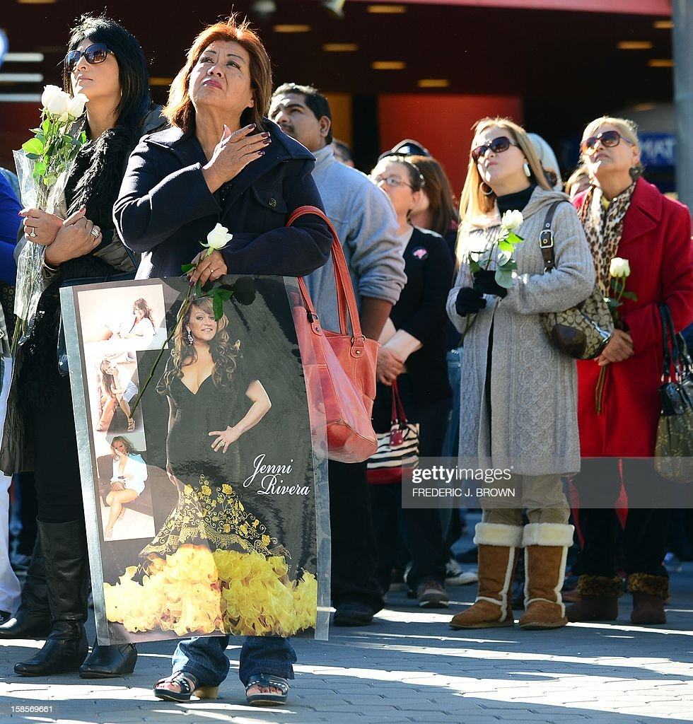 Fans of the late Mexican-American singer Jenni Rivera watch a live viewing of the memorial service at the Gibson Amphitheater in Universal City on December 19, 2012 in California. The service, billed by the Rivera family as a 'Celestial Graduation,'' was broadcast live and watched by her many fans off a big screen at a Universal CityWalk plaza. AFP PHOTO / Frederic J. BROWN