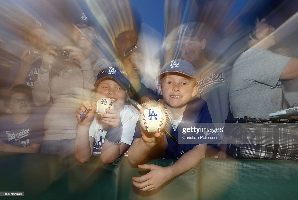 Fans of the Los Angeles Dodgers; Hailey and Zack Jones hold up baseballs to be autographed before the spring training game against the San Francisco Giants at Camelback Ranch on March 4, 2011 in Glendale, Arizona.