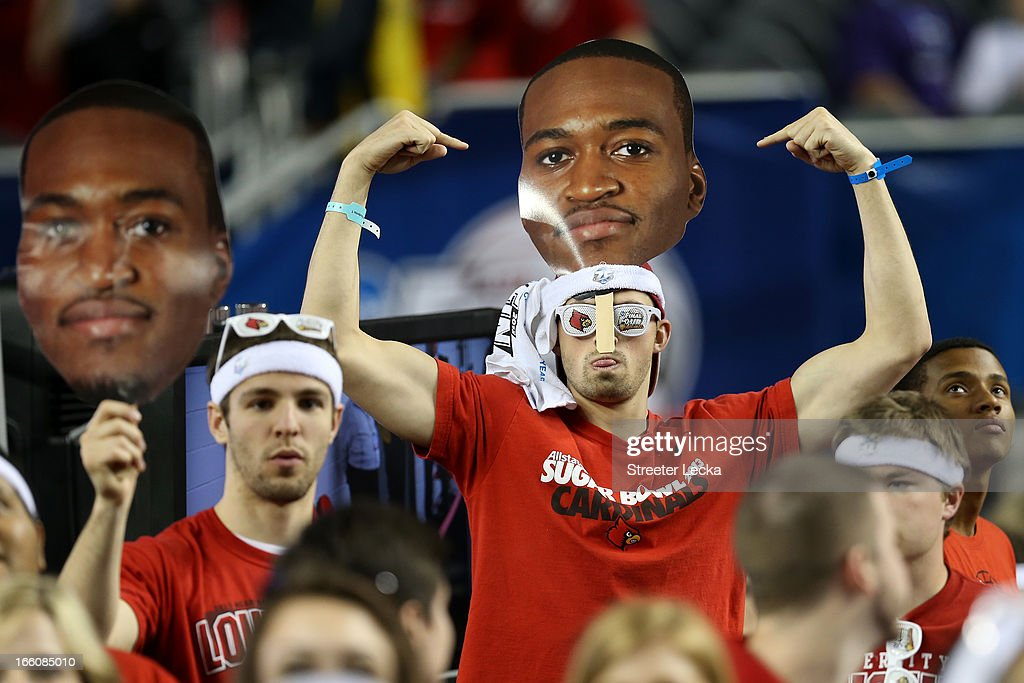 Fans of the Louisville Cardinals hold up signs with the likeness of Kevin Ware on them as they support their team against the Michigan Wolverines during the 2013 NCAA Men's Final Four Championship at the Georgia Dome on April 8, 2013 in Atlanta, Georgia.