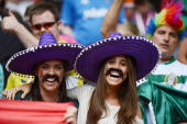 Fans of the Mexico's football team wear fake mustaches and a sombrero hat to cheer their team during the Men's football quarterfinal match between...
