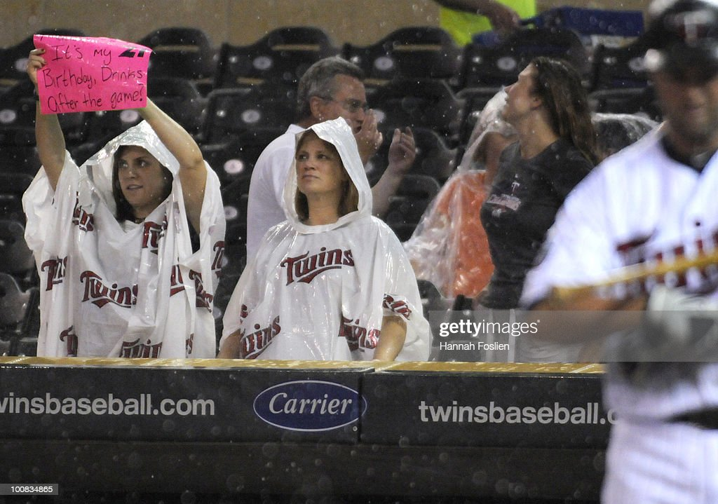Fans of the Minnesota Twins hold up signs as rain falls in the fifth inning against the New York Yankees during their game on May 25, 2010 at Target Field in Minneapolis, Minnesota.