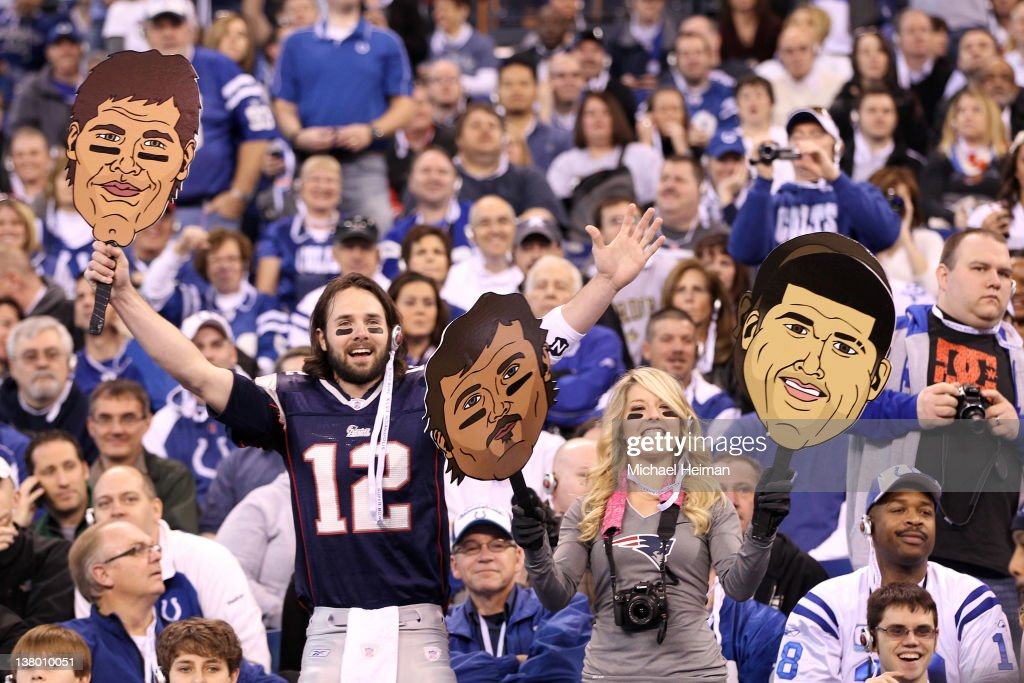 Fans of the New England Patriots hold up giant cartoon cutouts with the liknesses of New England Patriots players including Tom Brady (L) and Arron Hernandez (R) during Media Day ahead of Super Bowl XLVI against the New York Giants at Lucas Oil Stadium on January 31, 2012 in Indianapolis, Indiana.