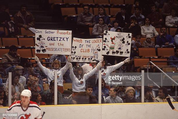 Fans of the New Jersey Devils professional hockey team hold up signs which mock Canadian hockey player Wayne Gretzky and his fellow Edmonton Oilers...