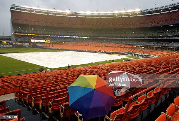 Fans of the New York Mets sit in the rain during a delay prior the start of the game against the Atlanta Braves on September 12 2008 at Shea Stadium...