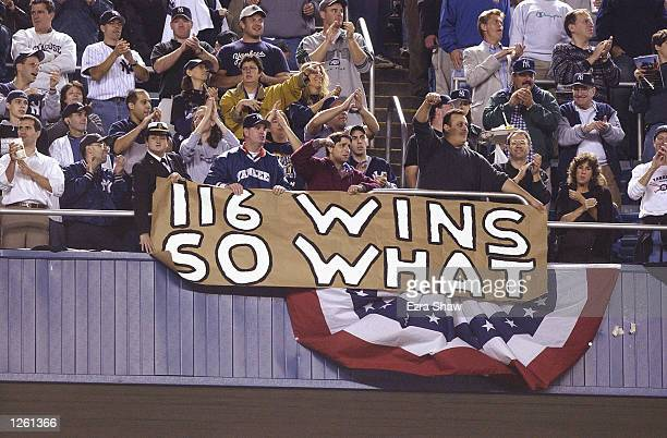 Fans of the New York Yankees stand and applaud in front of a sign referencing the Seattle Mariners regular season 116 victories during game five of...