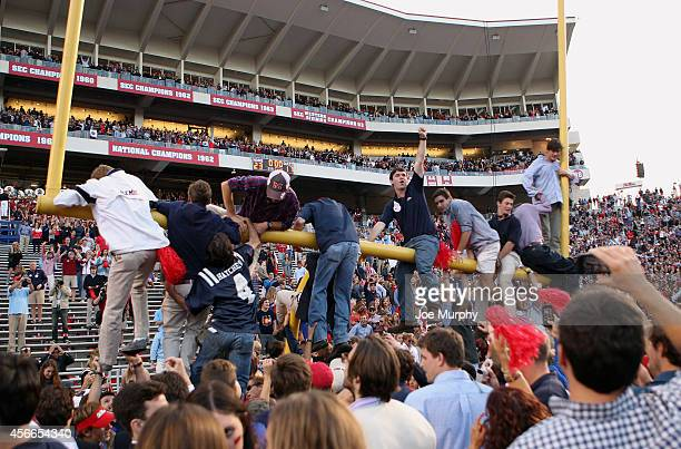 Fans of the Ole Miss Rebels hang on the goalpost while celebrating the victory over the Alabama Crimson Tide on OCTOBER 4 2014 at VaughtHemingway...