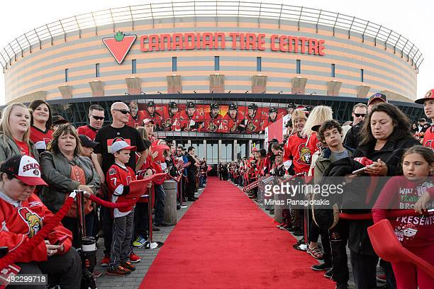 Fans of the Ottawa Senators lineup the red carpet waiting for the players prior to the NHL home opener game against the Montreal Canadiens at...