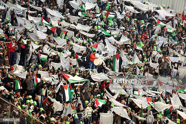 Fans of the Palestinian national team wave the national flag and the traditional chequerred keffiyeh during the AFC qualifying football match for the...
