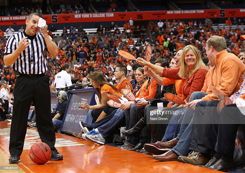 Fans of the Syracuse Orange waive posters of the face of head coach Jim Boeheim (not pictured) to fan the official as he wipes his forehead during a break in play in the game against the Detroit Titans at the Carrier Dome on December 17, 2012 in Syracuse, New York.