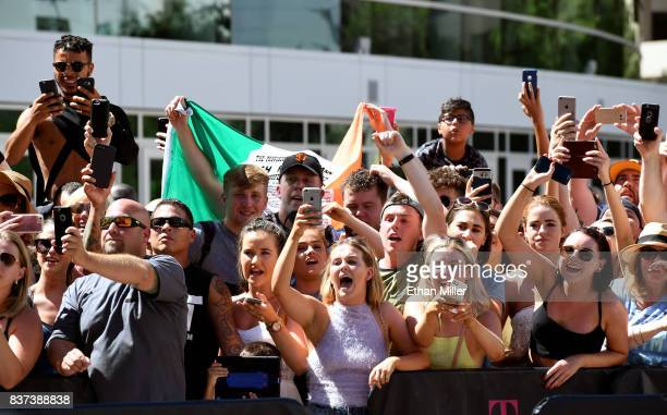 Fans of UFC lightweight champion Conor McGregor cheer as he arrives at Toshiba Plaza on August 22 2017 in Las Vegas Nevada McGregor will fight Floyd...