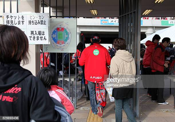 Fans of Urawa Red Diamonds enter into the stadium through the turnstiles / gates