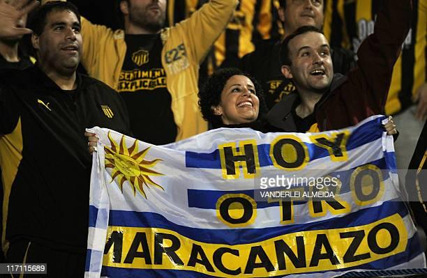Fans of Uruguay's Penarol cheer their team before the start of the Copa Libertadores second leg final match against Santos FC at Pacaembu stadium in...