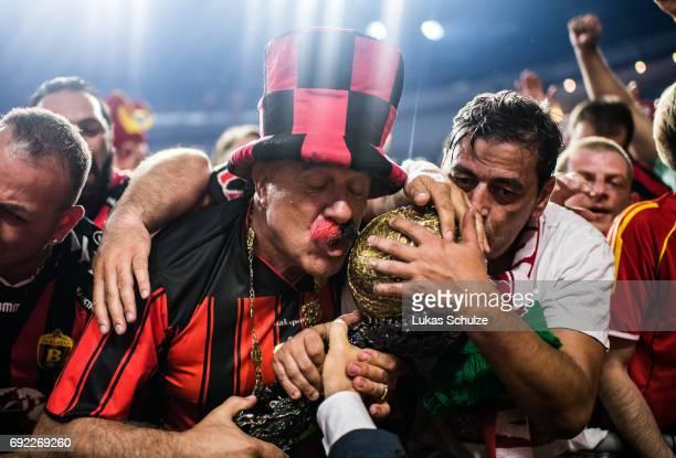 Fans of Vardar kiss the trophy after winning the VELUX EHF FINAL4 Final match between Paris SaintGermain Handball and HC Vardar at Lanxess Arena on...