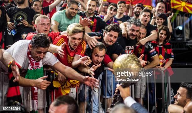 Fans of Vardar reach for the trophy after winning the VELUX EHF FINAL4 Final match between Paris SaintGermain Handball and HC Vardar at Lanxess Arena...