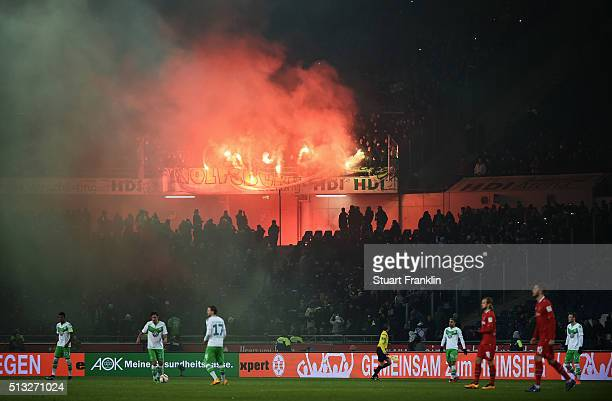 Fans of Wolfsburg burn flares during the Bundesliga match between Hannover 96 and VfL Wolfsburg at HDIArena on March 1 2016 in Hanover Germany