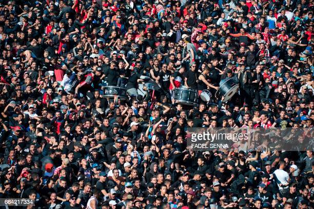 Fans of Wydad Athletic Club cheer during a match against Far Rabat at the Stadium of Casablanca on April 3 2017 / AFP PHOTO / FADEL SENNA