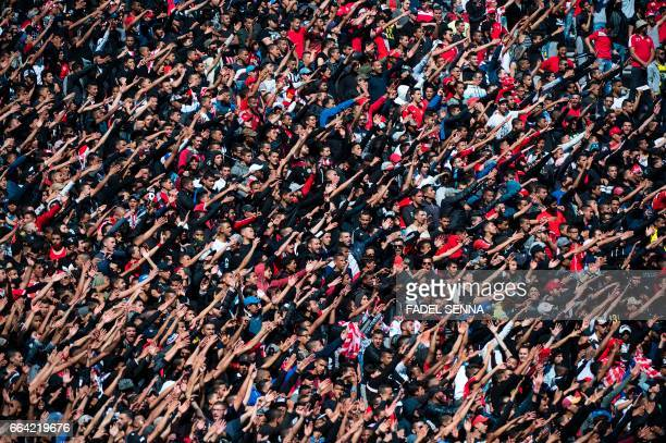 TOPSHOT Fans of Wydad Athletic Club cheer during a match against Far Rabat at the Stadium of Casablanca on April 3 2017 / AFP PHOTO / FADEL SENNA