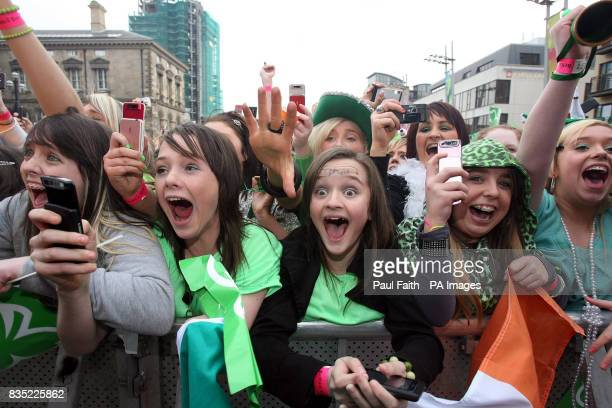 Fans of X Factor Finalist Eoghan Quigg cheer as he performs during the St Patricks Day celebrations in Belfast where thousands of people were...