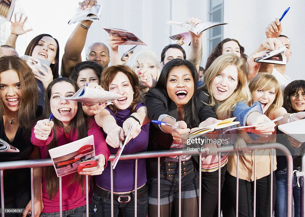 Fans offering notepads for celebrity's signature behind barrier
