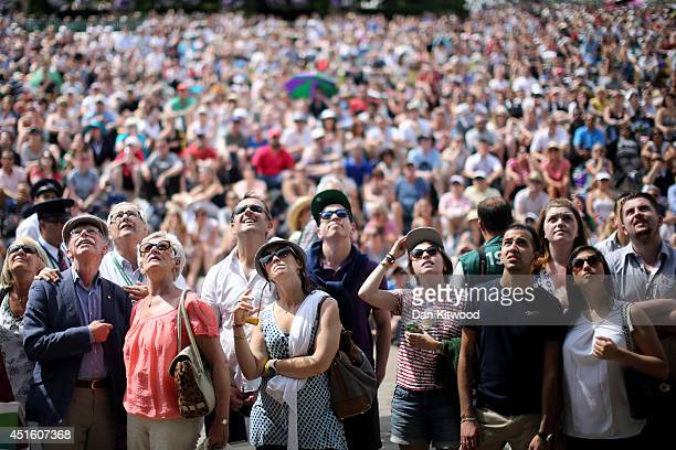 Fans on Murray mound look up at the big screen as they watch the Andy Murray against Grigor Dimitrov match on day nine the Wimbledon Lawn Tennis...