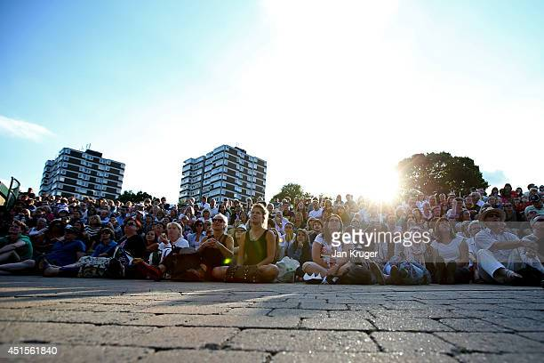 Fans on Murray Mound sit in the late evening sunshine to watch the centre court action on the big screen on day eight of the Wimbledon Lawn Tennis...